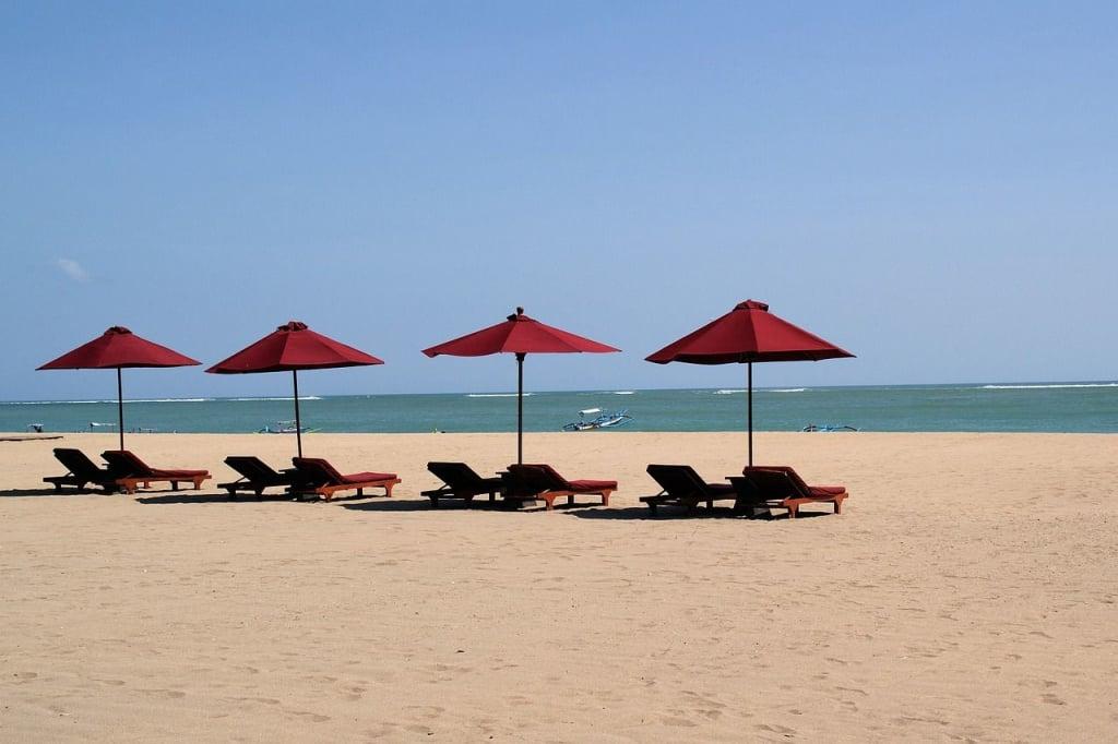 Pantai Kuta Bali Pasir Putih Tenda dan kursi Merah Menghadap Laut Biru Kapal Siang Hari Horizon