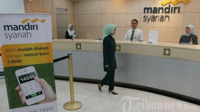 Orang Kerja di Bank Teler atau Kasir Mandiri Syariah Laki-Laki-Wanita Berdiri Kas